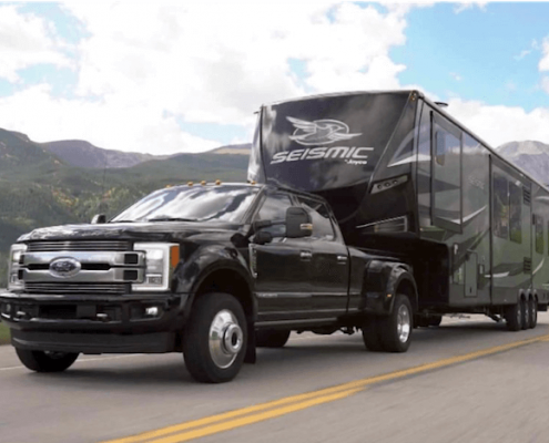 black ford pickup truck towing a camping trailer